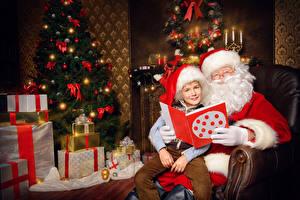 Photo New year New Year tree Present Santa Claus Boys Winter hat Sit child