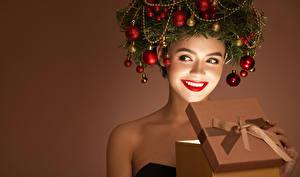 Fotos Neujahr Originelle Farbigen hintergrund Lächeln Rote Lippen Geschenke Ast Kugeln junge frau