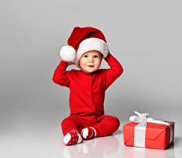 Pictures Christmas Gray background Boys Uniform Winter hat Gifts Staring Sitting Children