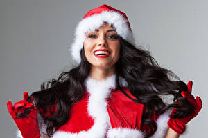 Photo Christmas Gray background Brunette girl Winter hat Smile Staring Glove Red lips young woman