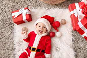 Hintergrundbilder Neujahr Baby Uniform Mütze Geschenke Lächeln Schneeflocken kind