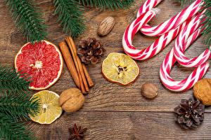 Picture Christmas Lollipop Cinnamon Nuts Lemons Grapefruit Wood planks Conifer cone Branches