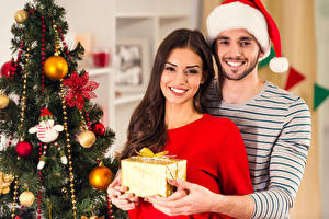 Photo New year Man 2 Brown haired Smile Staring Winter hat Present New Year tree Hands young woman