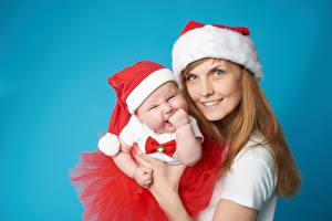 Fotos Neujahr Mutter Farbigen hintergrund Lächeln Mütze Baby Starren Mädchens