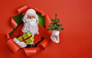Fotos Neujahr Weihnachtsmann Geschenke Christbaum Bärte Uniform Roter Hintergrund