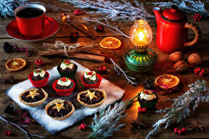 Pictures New year Still-life Kettle Coffee Candles Little cakes Cinnamon Nuts Boards Cup Branches Food