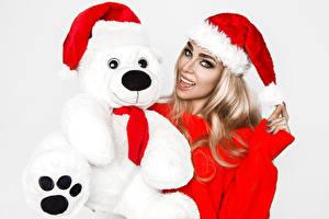 Fotos Neujahr Teddybär Weißer hintergrund Blondine Mütze Blick junge frau