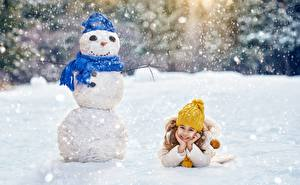 Photo New year Winter Snowman Little girls Lying down Smile Winter hat Scarf Snow child