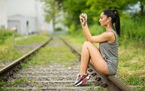 Pictures Blurred background Rails Sit Hands Tattoos Legs Brunette girl Girls