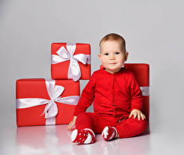 Pictures New year Gray background Baby Present Red Bow knot Staring Sit child