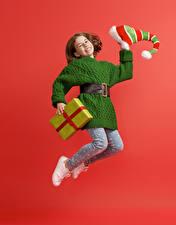 Fotos Neujahr Kleine Mädchen Geschenke Kleid Mütze Sprung Lächeln Roter Hintergrund Kinder