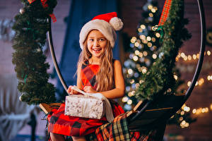Bilder Neujahr Kleine Mädchen Mütze Geschenke Lächeln Sitzt Starren kind