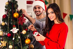 Fotos Neujahr Mann Braune Haare Weihnachtsbaum Kugeln Lächeln Starren Hand junge frau