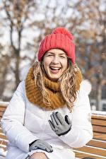 Fotos Winter Sitzt Mütze Jacke Handschuh Lacht Schal junge frau