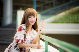 Bilder Asiaten Unscharfer Hintergrund Hand Kleid Lächeln Braune Haare Niedlich Starren junge frau