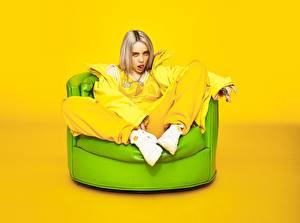 Bilder Farbigen hintergrund Sessel Sitzt Blond Mädchen Blick Billie Eilish Prominente Mädchens