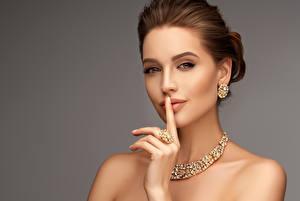 Fotos Schmuck Finger Halsketten Grauer Hintergrund Braune Haare Gesicht Ohrring junge frau