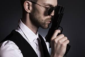 Fotos Mann Pistole Grauer Hintergrund Seitlich Brille Hand Bärtiger