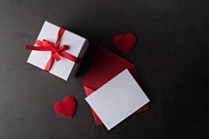 Fotos Valentinstag Grauer Hintergrund Vorlage Grußkarte Blatt Papier Geschenke Herz Schleife