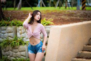 Bilder Asiatische Bokeh Posiert Shorts Bauch Hand Braunhaarige  junge frau