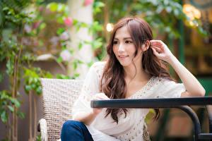 Fotos Asiaten Unscharfer Hintergrund Sitzt Hand Braune Haare junge frau