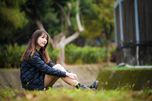 Picture Asiatic Blurred background Sit Legs Jacket Brown haired young woman