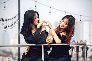Fotos Asiaten Unscharfer Hintergrund 2 Hand Lächeln Brünette Braune Haare Herz junge frau