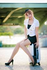 Hintergrundbilder Asiatische Posiert Sitzt Koffer High Heels Bein Schönes Rock Bluse Uniform Flugbegleiter Braune Haare junge frau