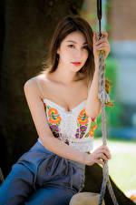 Bilder Asiatisches Sitzen Braunhaarige Starren Bokeh junge frau