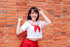 Picture Asian Wall Made of bricks Pose Hands Skirt Blouse Smile Eyeglasses Schoolgirl young woman