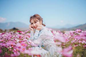 Fotos Grünland Asiaten Unscharfer Hintergrund Sitzt Kleid Hand Lächeln Niedlich Braune Haare Starren junge frau Natur Blumen
