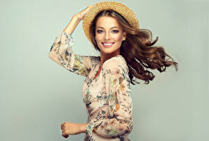Fotos Grauer Hintergrund Braune Haare Lächeln Blick Der Hut Hand Model Haar junge Frauen