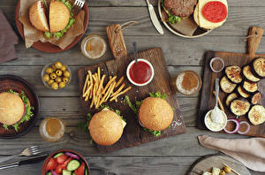 Pictures Hamburger Vegetables Olive Buns French fries Beer Fast food Wood planks Cutting board Ketchup Highball glass Food