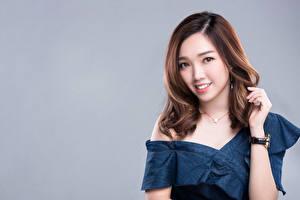Fotos Asiatisches Farbigen hintergrund Hand Lächeln Braunhaarige Starren Frisuren Haar Mädchens
