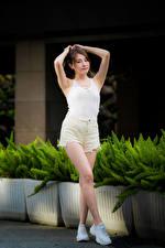 Fotos Asiatische Pose Bein Shorts Unterhemd Hand Braunhaarige junge frau