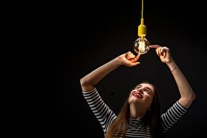 Pictures Black background Light bulb Hands Smile Brown haired young woman