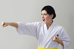 Fotos die Faust Grauer Hintergrund Hand Schreiendes Schreien Uniform Schlag Karate Mädchens
