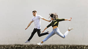 Pictures Man 2 Jump Hands Brown haired Jeans young woman