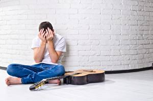Photo Men Walls Made of bricks Sitting Jeans T-shirt Hands Guitar Sadness