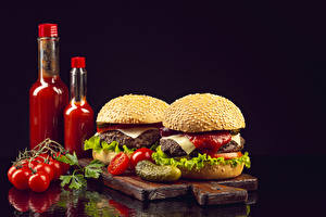 Pictures Tomatoes Hamburger Cucumbers Buns Black background Bottles Ketchup Cutting board