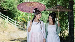 Bilder Asiatische Zwei Brünette Regenschirm Niedlich Mädchens