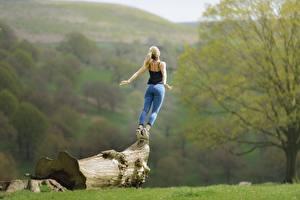 Fotos Blondine Jeans Posiert Holzstamm Unscharfer Hintergrund Hinten junge frau