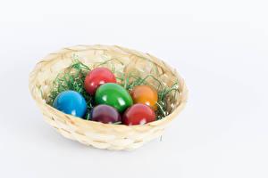 Bilder Ostern Weißer hintergrund Weidenkorb Ei Mehrfarbige Lebensmittel