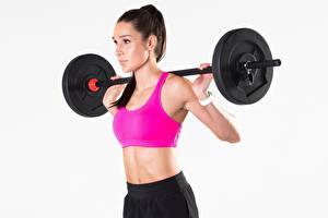 Bilder Fitness Hantelstange Grauer Hintergrund junge frau Sport