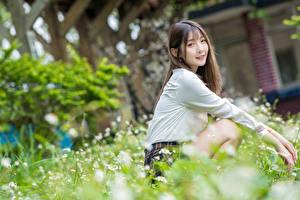 Bilder Asiatische Unscharfer Hintergrund Sitzt Lächeln Blick Mädchens