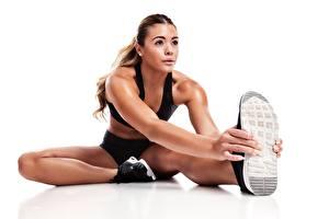 Bilder Fitness Weißer hintergrund Sitzt Bein Dehnübung Schuhsohle sportliches Mädchens