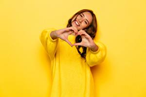 Pictures Gestures Brown haired Smile Happy Sweater Yellow Hands Heart young woman