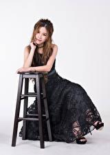 Fotos Asiatische Braune Haare Stühle Sitzend Kleid Blick Grauer Hintergrund Mädchens