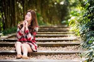 Fotos Asiatisches Braune Haare Sitzend Bein Kleid Unscharfer Hintergrund Mädchens