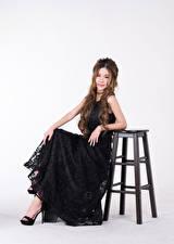 Fotos Asiaten Stuhl Sitzt Kleid Schwarz Blick Grauer Hintergrund Mädchens